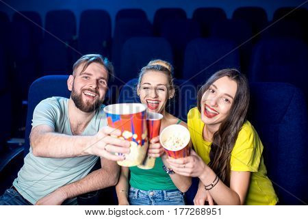Happy friends having fun sitting together with popcorn in the cinema