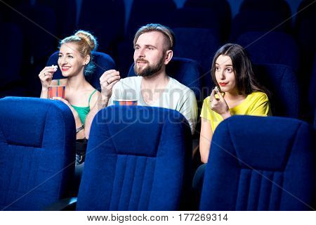 Friends watching film sitting together with popcorn in the cinema