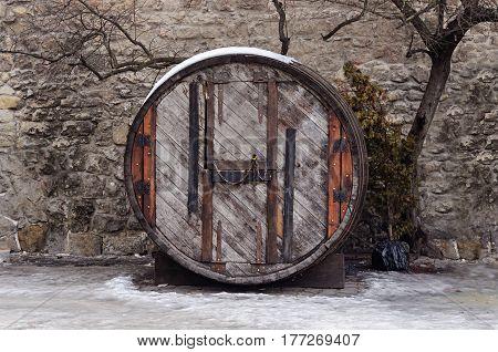 Old big oak barrel-shop on the stone wall background in Lviv Ukraine