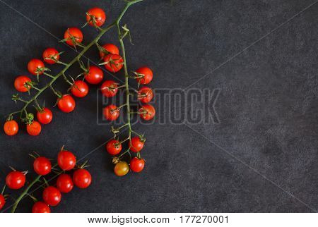 Bunch of cherry tomatoes on a black background