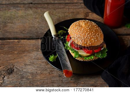 Homemade burger with beef salad and tomato sauce on a black plate on a wooden background. Fast food.