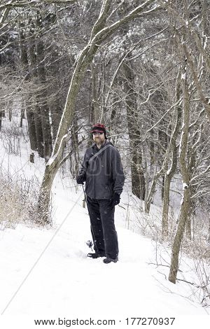 Rugged outdoorsman hiking through snow covered forest looking for fishing winter scene
