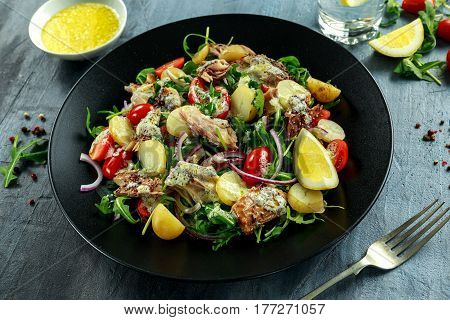 Smoked Mackerel Salad with warm boiled new potato, cherry tomatoes, chopped red onion and Ruccola on black plate