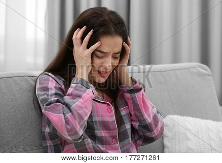 Depressed woman crying on sofa indoors