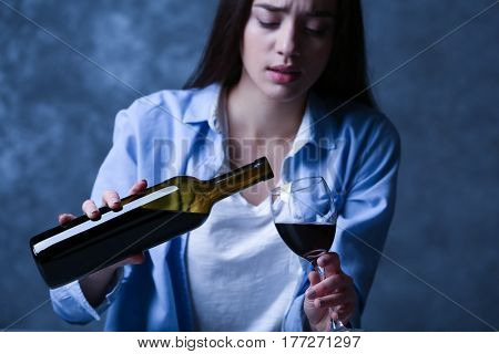 Depressed young woman drinking wine on grey wall background
