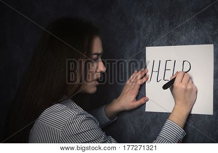 Woman writing word HELP on paper on grey wall background