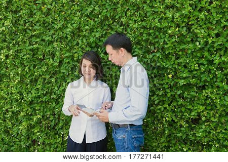 Businessman and businesswoman discussing work while walking.