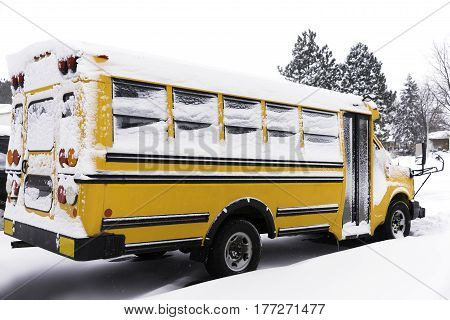 Yellow school bus covered with snow parked in a residential neighborhood on a snow day