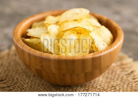 Hearty potato crisps served in a wooden bowl.