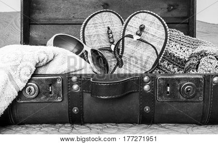 Black and white image of vintage leather suitcase packed with travel items for tropical vacation spilling out