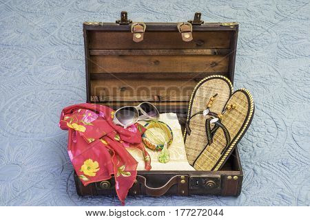 Small vintage suitcase packed full of items for a tropical holiday including towel scarf and sandals travel concept
