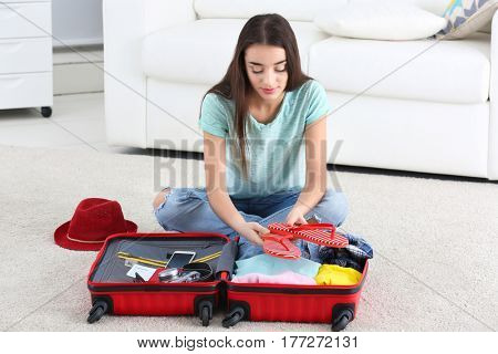 Beautiful young woman packing suitcase at home