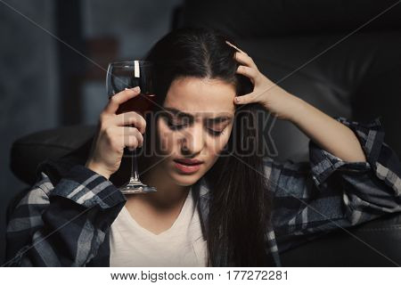 Depressed young woman drinking wine indoors