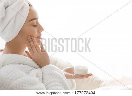 Beautiful young woman applying cream onto skin in spa salon