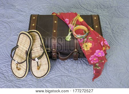 Vintage suitcase with sandals bracelet scarf and necklace draped on it tropic travel concept