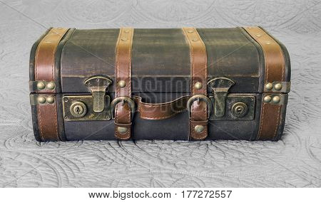 Vintage leather suitcase with brass locks closed and sitting on bed old fashioned travel concept