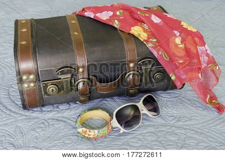 Vintage suitcase with tropical print floral scarf bracelet and sunglasses travel concept