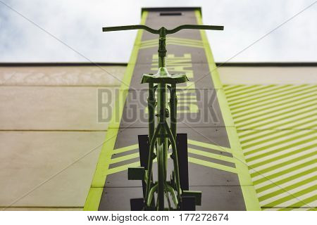 An old painted bicycle is going to the sky in the building. Modern image