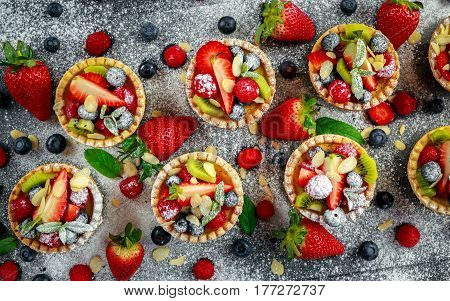 Berry tartlets with blueberries, raspberries, kiwi, strawberries, almond flakes in icing sugar