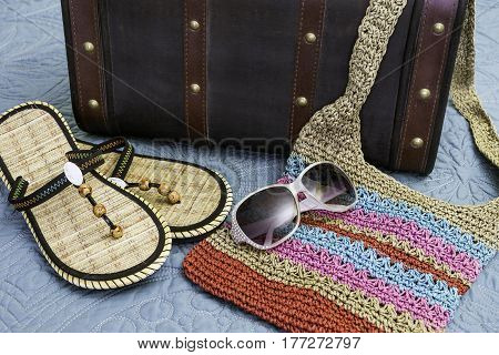Sandals sunglasses and tropical weave purse lying on bed ready for travel vintage suitcase background