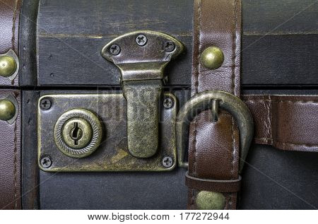 Closeup of brass lock and leather strap on vintage suitcase travel concept