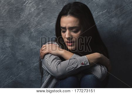 Depressed young woman on grey wall background