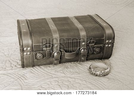 Old fashioned suitcase and floral bangle bracelet in sepia tone vintage travel concept