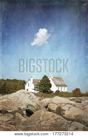A small white cloud hangs over the white Chapel of Port au Persil, Saint-Simeon, Quebec, Canada. Textured, retro style.