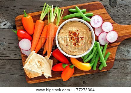 Hummus Dip With A Serving Platter Of Fresh Vegetables, Above View On A Wood Background