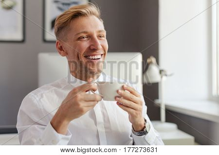 Smiling young blond man having a cup of hot beverage. Horizontal indoors shot.