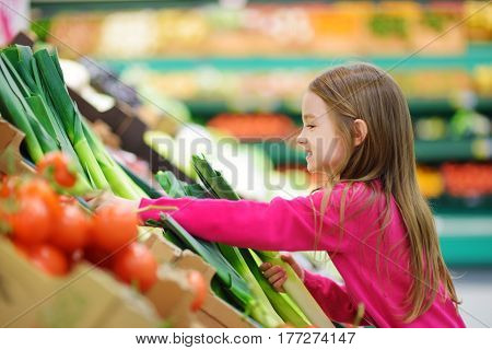 Little Girl Choosing Fresh Leek In A Food Store