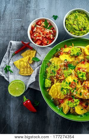 Nachos with cheese, jalapeno peppers, red onion, parsley, tomato, salsa, guacamole sauce and tequila on green plate