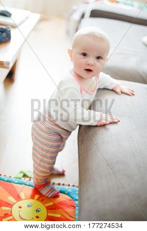 A Baby Is Standing Leaning On A Sofa