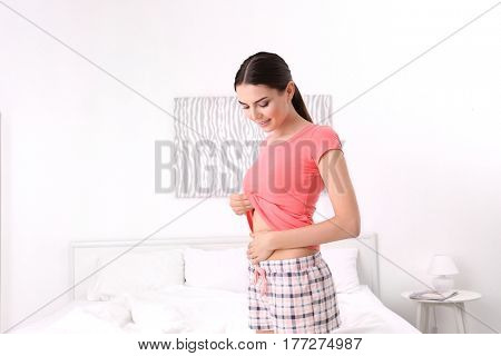 Beautiful young pregnant woman at home