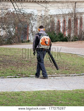 man in the park with hand leaves blower cleaning the walkwayan with leaves blower