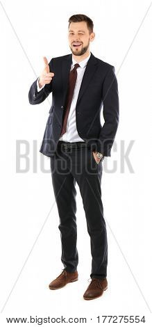 Handsome businessman in elegant suit winking and pointing on white background