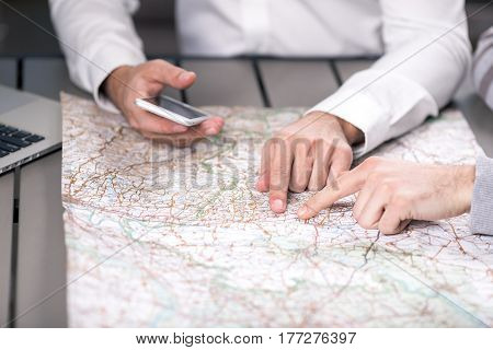 People choosing destination on the map in travel agecy