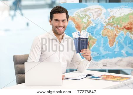 Young man tour agent sitting in office