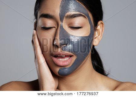 closeup portrait of woman feeling pleasure during facial mask treatment