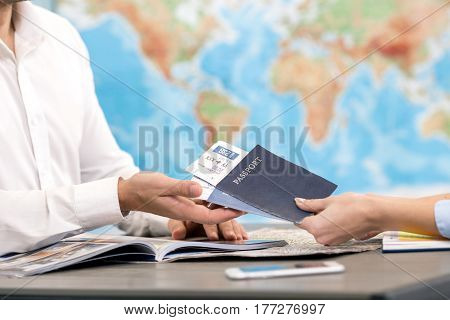 Young man tour agent giving passports and tickets to customer