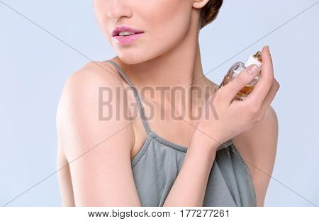 Beautiful young woman with bottle of perfume on color background, closeup
