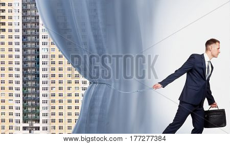 A businessman who represents the possibility of a profitable purchase of a new residential. He pulls back the curtain, which hides the new buildings of the city.