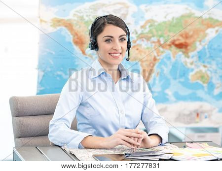Young woman sitting in office travel agency