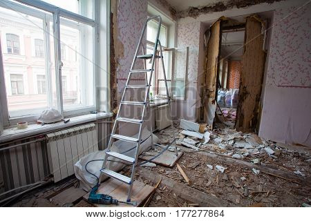 View of room of the apartment during under renovation remodeling and construction. Ladder garbage of constraction materials and lamp in dark room during of disassembling floors and walls.