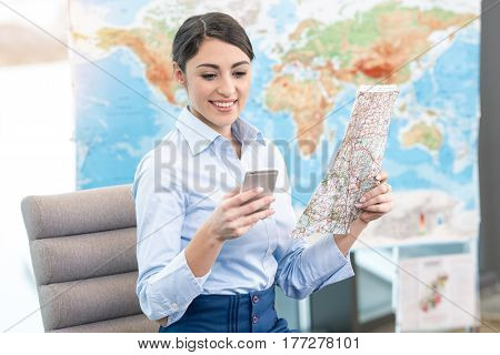 Young woman travel agent choosing destination with world map