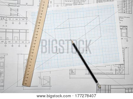 Open blueprints on wooden table background with a pencil and a ruler lying beside. Engineering and design. Construction projects. Planning.
