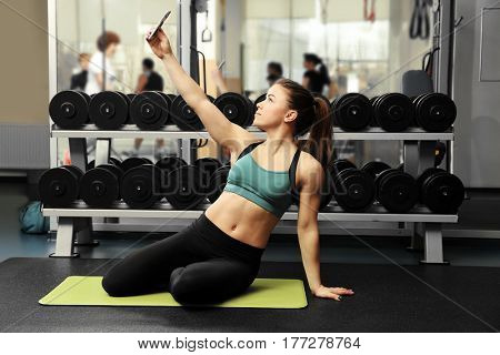 Young attractive woman taking selfie in gym