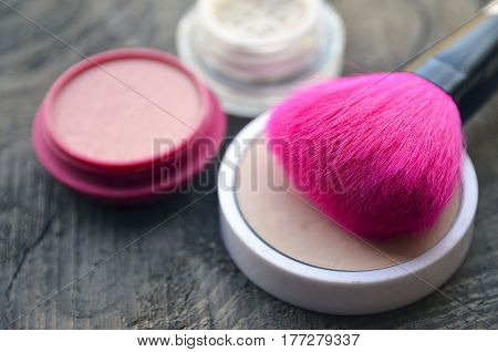 Pink makeup brush,compact powder and blush on old wooden background with copy space.Fashion cosmetic make-up or woman beauty accessories concept.Selective soft focus.