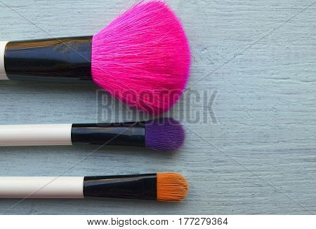 Makeup brushes on blue wooden background with copy space.Various make-up brushes set for makeup.Fashion cosmetic makeup or woman beauty accessories concept.Top view.Selective focus.