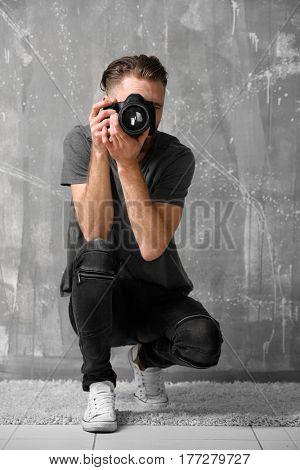 Handsome photographer near grunge wall
